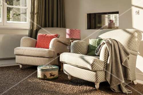 Traditional armchairs with beige covers next to window