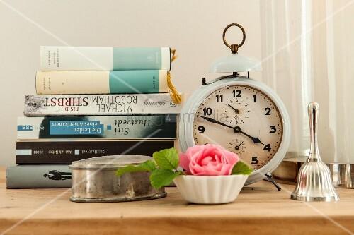 Silberdose und Rosendeko vor Bücherstapel und nostalgischem Wecker