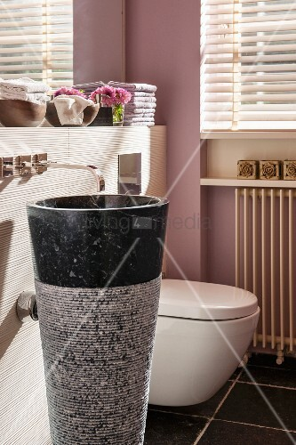 Conical stone pedestal sink with wall-mounted tap in modern bathroom