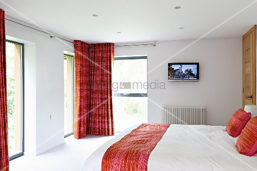 Modern white bedroom with red accents and double bed opposite French windows with floor-length curtains