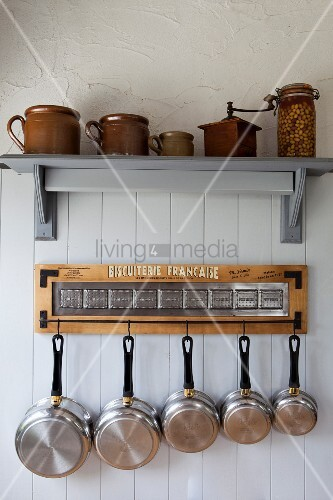Stoneware crockery on bracket shelf above collection of stainless steel pans hanging from rack
