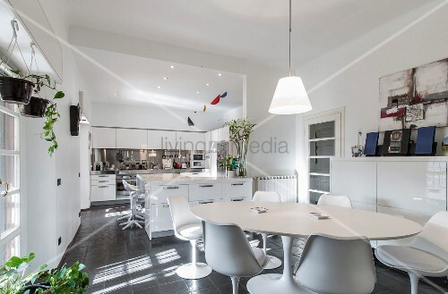 White dining set with classic table and shell chairs in front of open-plan kitchen