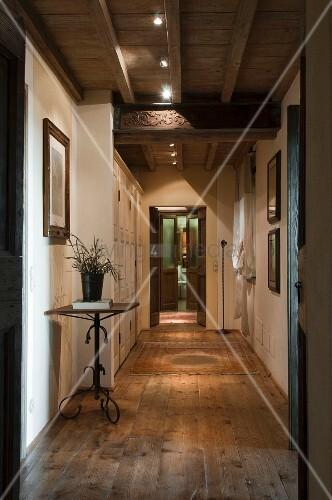 Langer Gang mit rustikalem Dielenboden, an Holzbalkendecke moderne ...