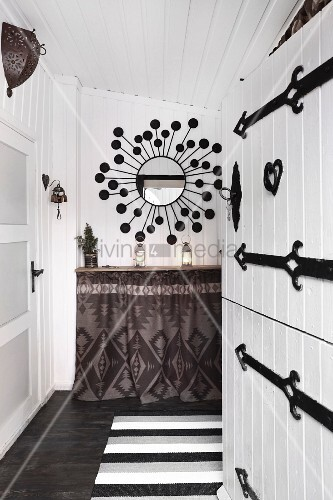 Ethnic-style entrance area with open white wooden door