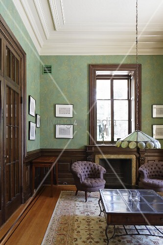 Green-painted interior with stucco ceiling and Art Nouveau Tiffany-style pendant lamp above table in foreground