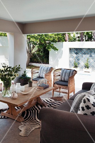 Roofed terrace with wicker chairs and African ornaments