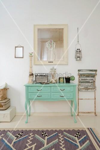 Grün lackierter Konsolentisch mit Vintage Kofferradio, Apothekerglas, Blechdose und angelehntem Vintage-Klappstuhl
