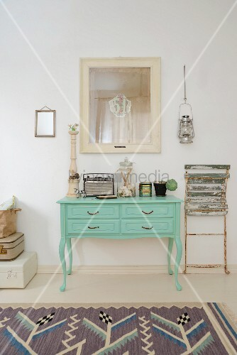 Vintage portable radio, apothecary bottles and tin on green-painted console table next to vintage folding chair leant against wall