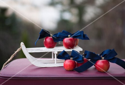 Red apples and dark blue ribbons on sledge ornament