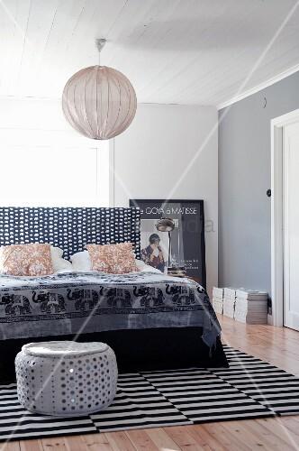 Schlafzimmer in schwarz-weissem Mustermix; auf Doppelbett Tagesdecke mit Elefantenmotiven und auf gestreiftem Teppich grau glitzernder Sitzpouf