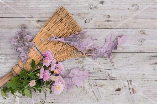 Pink chrysanthemums and autumnal oak leaves on besom broom
