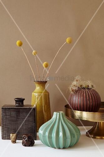 Herbstliches Stillleben mit Vasen, Trockenblumenzweig und Eulenfiguren