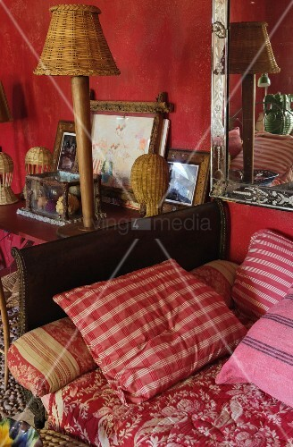 Striped cushions on daybed with leather-covered arm next to pictured and table lamp on table in vintage interior