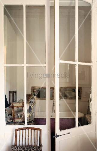 View through glass lattice doors into vintage bathroom with free-standing bathtub