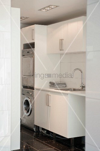 View into utility room with sink next to washing machine and drier integrated into cupboards