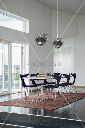 Dining area with modern chairs on ethnic rug below classic pendant lamps