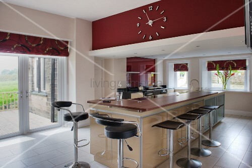 Island counter with red Corian worksurface and bar stools with black seas in open-plan kitchen