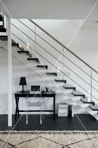 Schreibtisch mit Ghoststuhl unter Treppenlauf in zeitgenössischem Treppenhaus