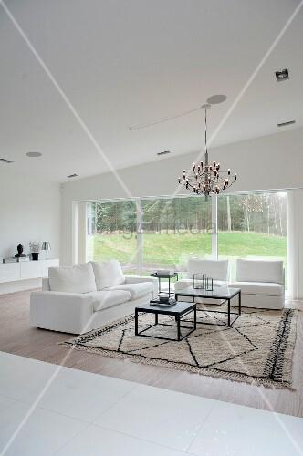 Eleganter, weisser Zweisitzer und passende Sessel um zweiteiliges Couchtisch-Set auf Teppich, moderner Lüster, im Hintergrund Glasfront mit Ausblick