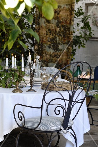 Ornate metal chair at table festively set with white tablecloth