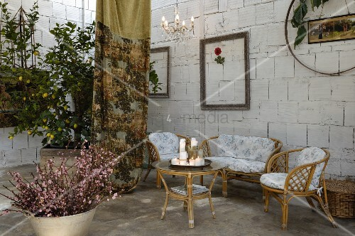 Seating area with pale wicker furniture and table against limestone wall