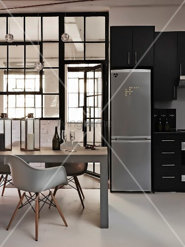 Classic chairs at dining table in front of glass partition, fridge-freezer in kitchen area and black fitted cabinets