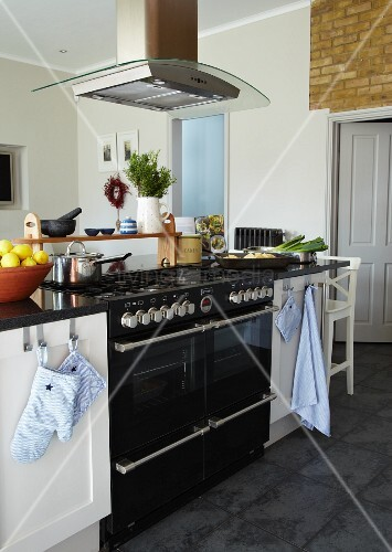 Island counter with black gas cooker and extractor hood in renovated kitchen with traditional ambiance