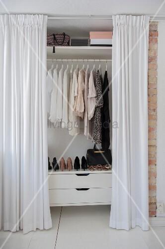 Open, floor-length white curtains screening wardrobe full of women's clothing