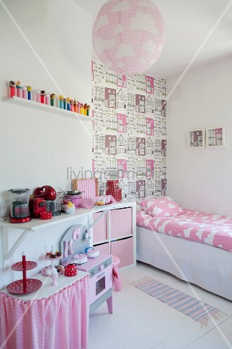 Girl's bedroom with pink accents, child's bed and section of wall with house-patterned wallpaper