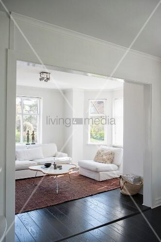Blick durch breiten Durchgang in gemütlichen weißen Wohnraum, Polstersessel und Sofa um Coffeetable mit organischer Tischplatte