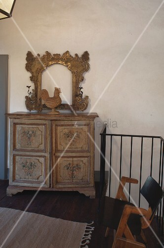 Carved cockerel and gilt frame on top of antique farmhouse cabinet on landing with balustrade