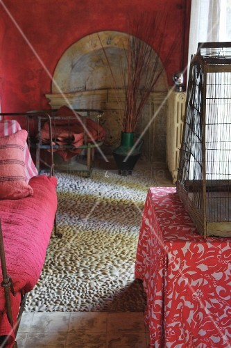 Mediterranean interior with red walls, pebble mosaic, daybed, birdcage and floral tablecloth on table