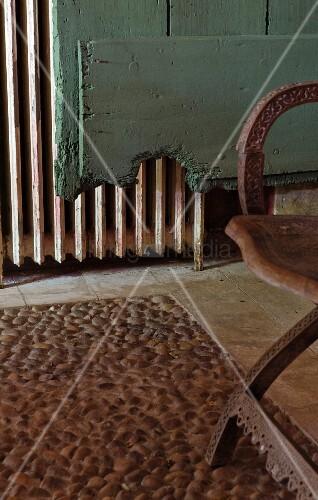 Steckkieselboden mit geschnitztem Stuhl vor türkisgrünem Vintagebrett und altem Heizkörper