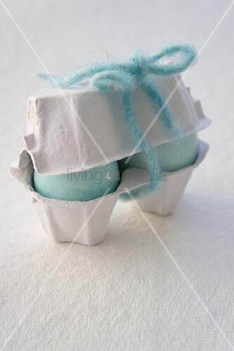 Pale blue Easter eggs in egg box
