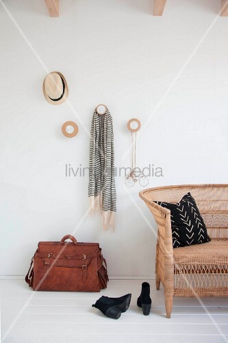 Cloakroom pegs made from round wooden discs, leather bag and wicker sofa