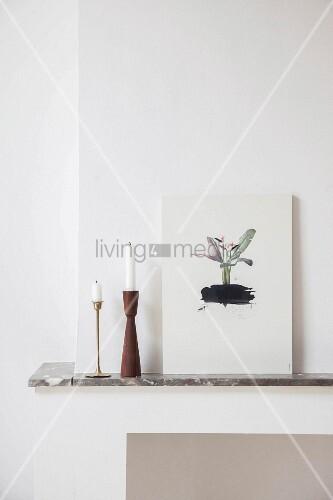 Kerzenständer und ein Bild auf dem Kaminsims