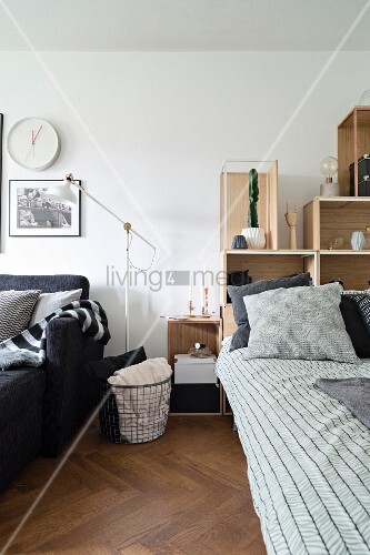 Bed with stacked shelving elements as headboard