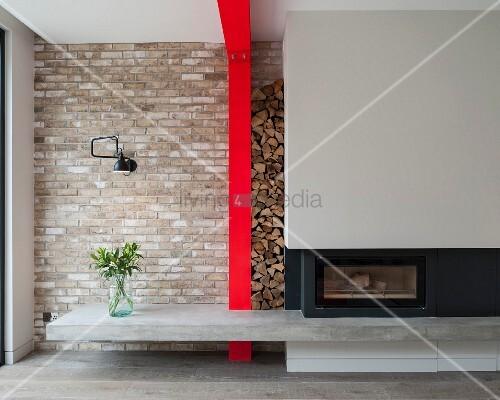 Moderner Kamin mit Betonablage und Holzlager zwischen grauer Kaminverkleidung und roter Stahlstütze an Ziegelwand