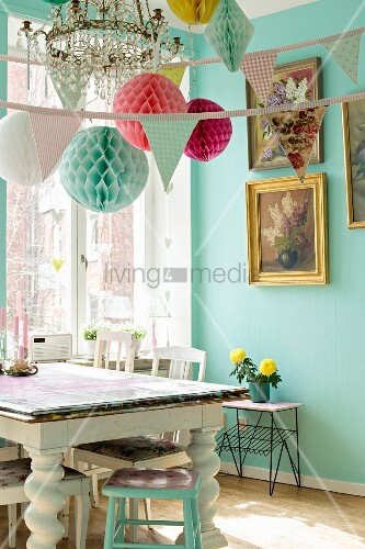 Dining room decorated with bunting and paper pompoms above vintage table with turned legs next to window