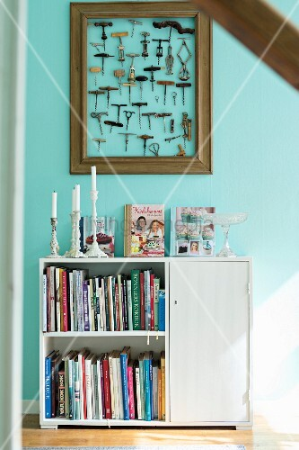 White half-height cabinet with books on shelves and candles on top against turquoise wall below framed collection of corkscrews