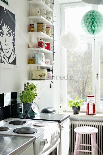 Küchenecke mit schwarz-weißem Pop Art-Poster und weißen Wandboards mit Vintage Aufbewahrungsdosen