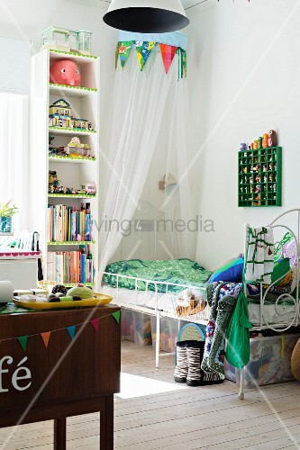 Spindly, white metal bed under canopy next to tall narrow shelving in girl's bedroom