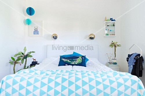 Double bed with blue and white bedspread and spherical wall lamps in retro-style bedroom