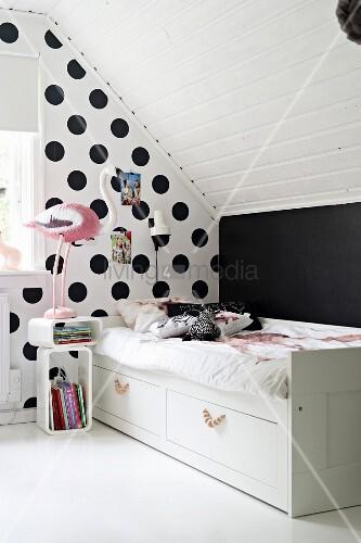 Bett im Kinderzimmer vor gepunkteter Wand