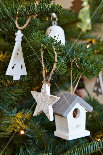 White-painted wooden Christmas decorations hanging on Christmas tree
