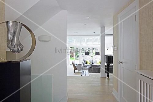 View from hallway into open-plan elegant interior with lounge area in front of terrace windows