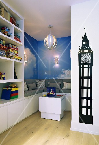 Play area with integrated bench, photo mural of clouds and collection of toys on white shelves; black wall sticker of Big Ben clock tower in foreground