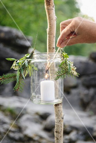 Lighting a candle in a hand-made lantern