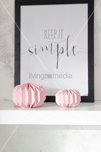 Pink paper ornaments and black-framed motto on white floating shelf