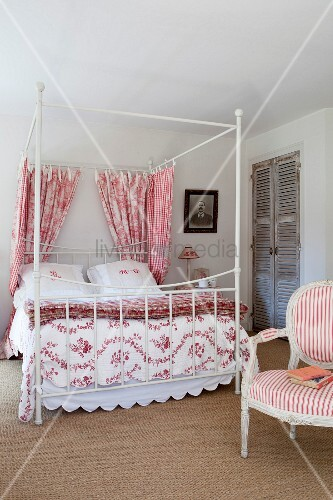 Four-poster bed decorated with red and white fabrics